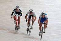 Three Cyclists Competing Each Other On Racing Track