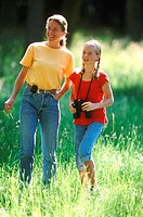 Mother and daughter hiking with binoculars