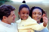 Interracial girl with parents waving