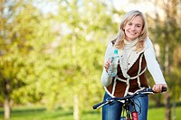 Attractive girl on a bicycle in the autumn park