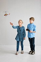 Boy and girl playing with helicopter model