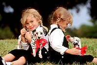 Twin girls with Dalmatian puppies