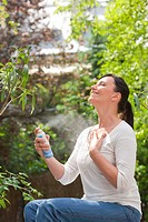 Woman spraying mist on face