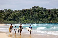 Surfers walking along the sea at Wizard Beach First Beach on Isla Bastimentos, Bocas del Toro, Panama