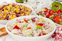 An assortment of salads on a buffet table  Potato salad, bean salad and fresh mixed salad arranged on a white table with glasses, cutlery and plates