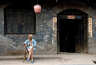 Old Chinese man sitting in of the traditional Streets of Pingyao, Shaanxi Province  China