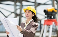 Architect reading blueprint in construction site
