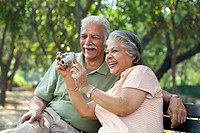 Smiling couple using digital camera at park