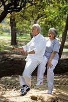 Playful couple having fun at park while sitting on tree trunk