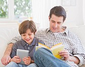 Father and son 10_11 years sitting on sofa with book and digital tablet