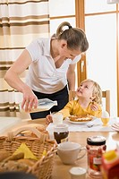 Mother pouring milk for daughter breakfast, smiling