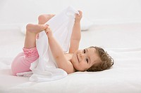 Baby girl lying on back and holding toes, smiling (thumbnail)