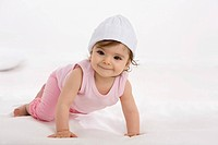 Baby girl crawling on baby blanket, smiling