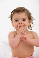 Baby girl with finger in mouth, portrait