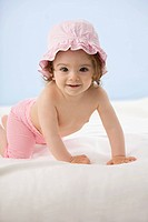 Baby girl crawling on blanket, smiling