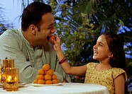 Girl feeding her father a laddoo