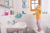 Girl standing on toilet, brushing teeth in bathroom