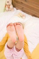 Girl lying on bed with feet up