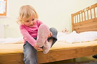 Girl sitting on bed and putting shoes (thumbnail)
