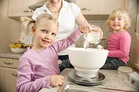 Mother and daughter preparing cake in kitchen