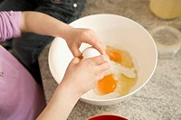 Girl breaking egg in bowl