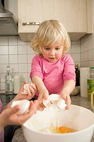 Girls pouring egg yolk in mixing bowl
