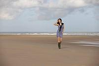 France, Pas_de_Calais, Escalles, Young woman strolling on empty beach