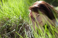 Young woman among green grass