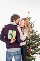 Mid adult man hiding gift from woman, smiling