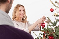 Woman preparing Christmas tree, smiling