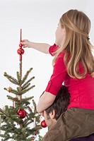 Girl sitting on man's shoulders and positioning tree topper