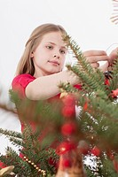 Girl positioning Christmas bauble on tree, close up