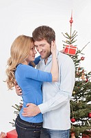 Mid adult couple embracing while woman holding gift, smiling