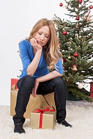 Mid adult woman sitting on gift with sad face