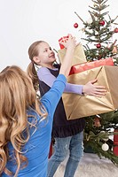 Daughter holding stack of gifts while mother adjusting