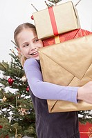Girl holding stack of Christmas gifts, smiling