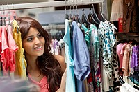 Smiling young woman at dress store