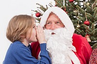 Boy whispering in Santa Claus ear, close up