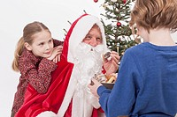 Girl leaning on Santa Claus shoulder, boy offering cookies