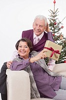 Senior couple leaning on sofa and woman showing christmas gift, smiling, portrait