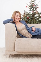 Mid adult woman leaning on sofa, smiling, portrait