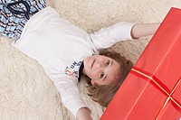 Boy lying on back and holding Christmas gift, smiling