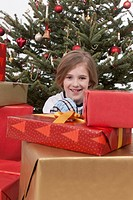 Boy sitting between Christmas gifts and tree, smiling, portrait