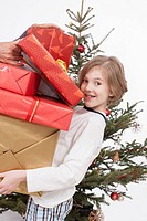 Boy holding stack of Christmas gifts, smiling, portrait