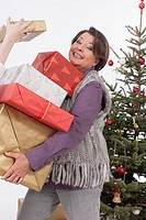 Senior woman holding stack of Christmas gifts, smiling, portrait