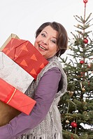 Senior woman holding Christmas gifts, smiling, portrait