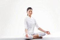 Smiling young woman meditating