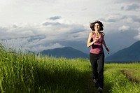 USA, Montana, Whitefish, Woman jogging on mountain path