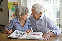 Germany, Bavaria, Senior couple with photo album, smiling (thumbnail)