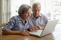 Germany, Bavaria, Senior couple using laptop at home